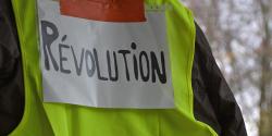 """Personne portant un gilet jaune avec l'inscription """"Révolution"""""""